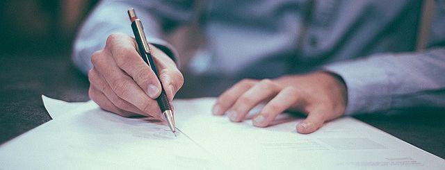 Foto de una persona firmando un contrato